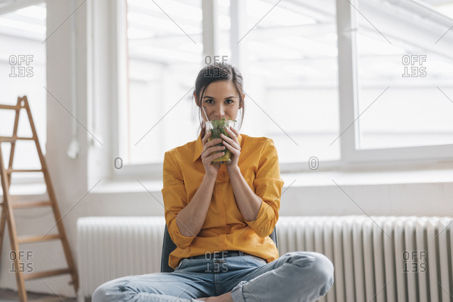 Young woman sitting in her new flat drinking tea