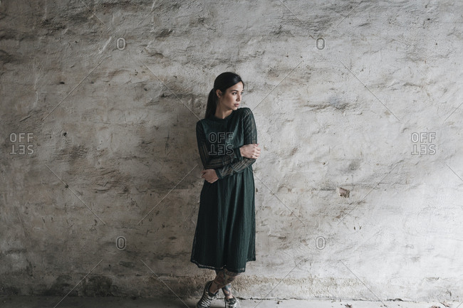 Young woman wearing green dress- standing in front of wall