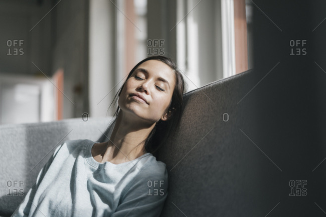 Young woman sitting on couch- taking a nap