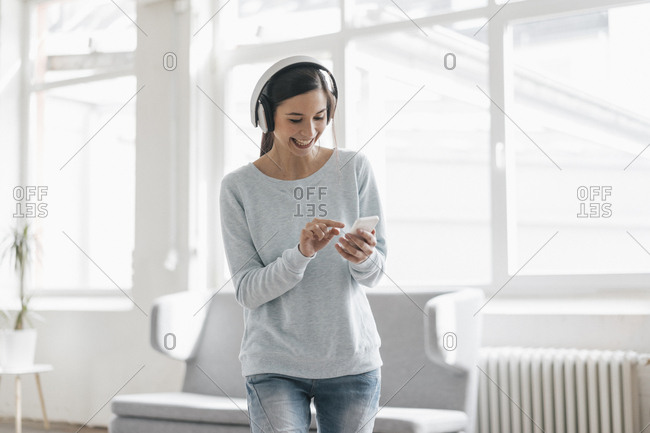 Young woman making a video call from her mobile phone- wearing headphones