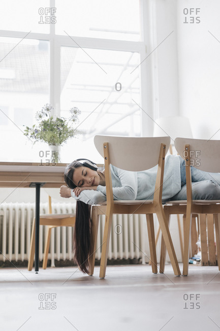 Young woman sleeping on chairs wearing headphones