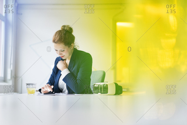 Businesswoman sitting at desk with VR goggles