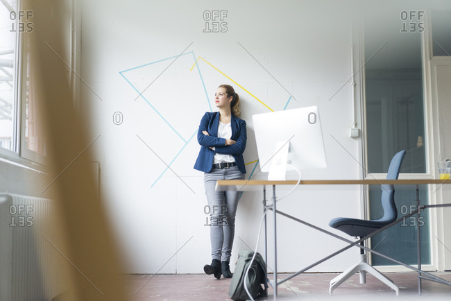 Businesswoman standing in office with arms crossed