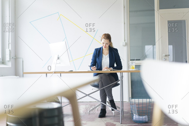 Businesswoman working at desk in her office