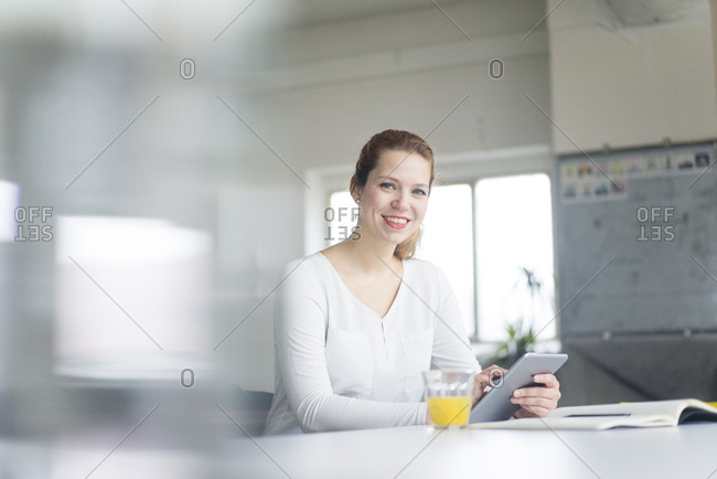 Businesswoman working at desk in her office- using digital tablet