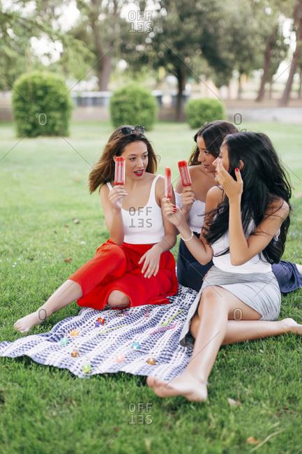 Friends in a park enjoying popsicles