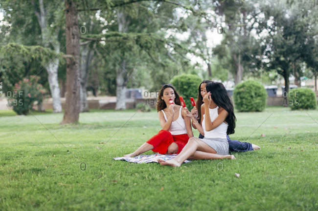 Friends in a park enjoying popsicles