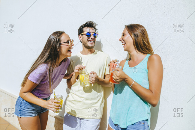 Laughing friends holding refreshing drinks in front of white wall