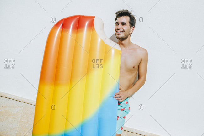 Man with ice cream float in front of white wall