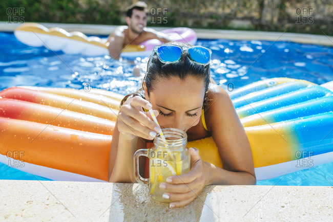Young woman in swimming pool with drink at the poolside