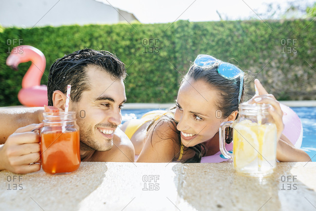 Happy couple in swimming pool with drinks at the poolside