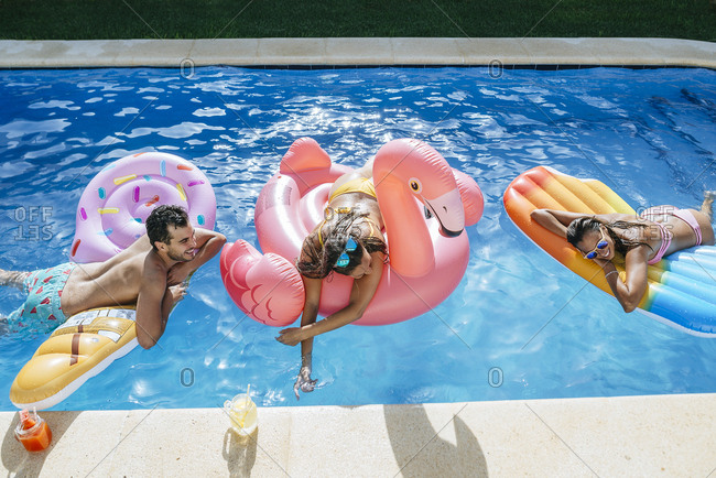 Happy friends on floats in swimming pool