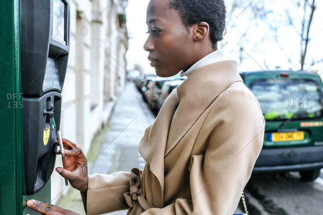 France- Paris- Young woman paying with her smartphone at parking automat