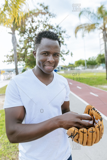 Portrait of smiling young man with ball and baseball glove