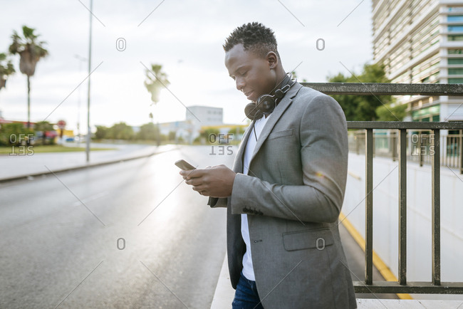 Young man standing at roadside looking at smartphone