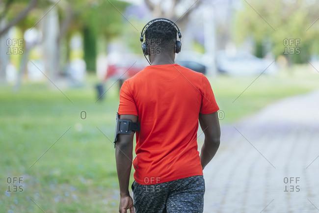 Back view of walking man in sportswear listening  music with headphones