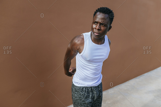 Man doing stretching exercises against brown wall