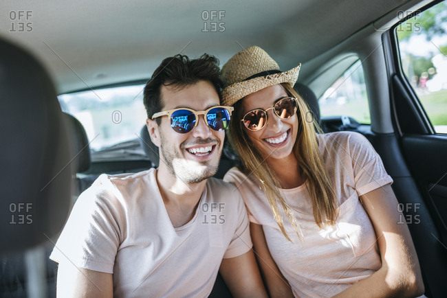 Couple laughing in the back seat of a car