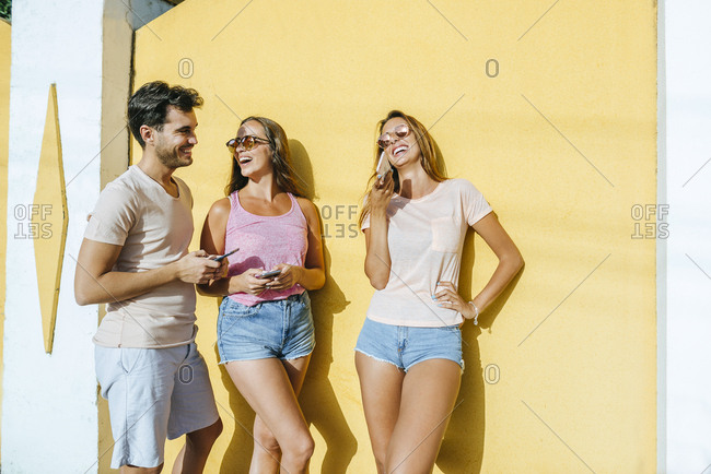 Three happy friends with cell phones outdoors