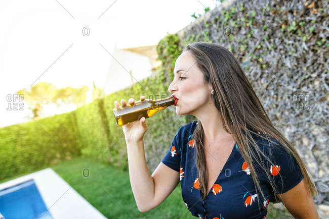 Young woman drinking beer at the poolside