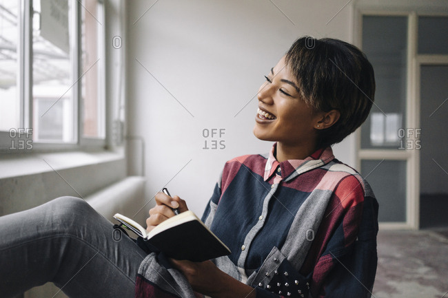 Smiling woman sitting at the window with notebook