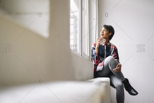Woman sitting at the window holding cup