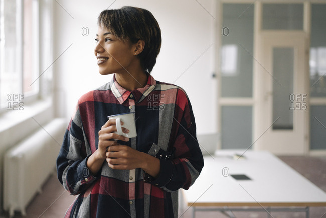 Smiling young woman holding cup