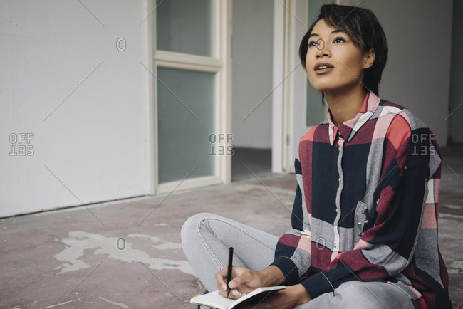 Woman sitting on cracked floor with notebook