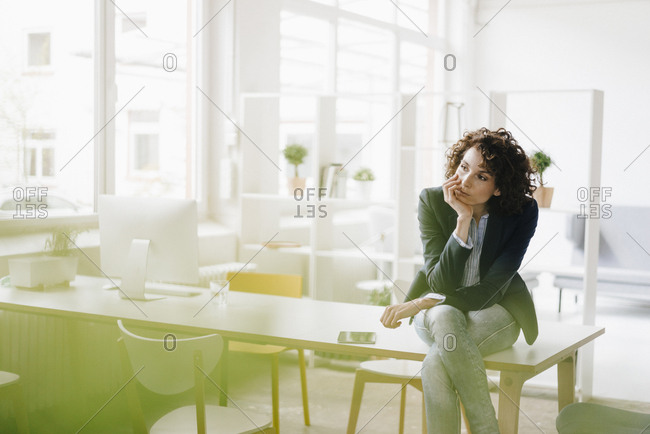 Businesswoman in office sitting on desk- looking worried