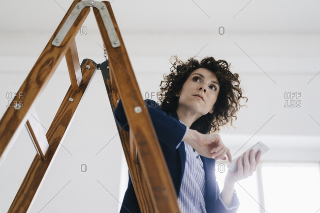 Businesswoman standing by ladder in office- holding smartphone