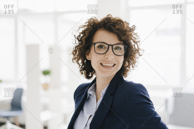 Businesswoman standing in her office- smiling