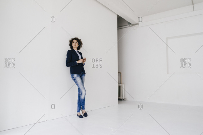 Businesswoman standing in loft - leaning against wall