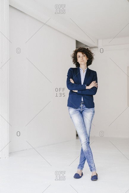 Businesswoman standing in loft with arms crossed
