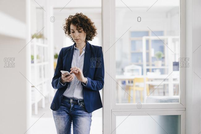 Businesswoman standing in office door- using smartphone