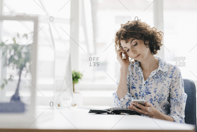 Businesswoman in office with smartphone and diary- looking worried