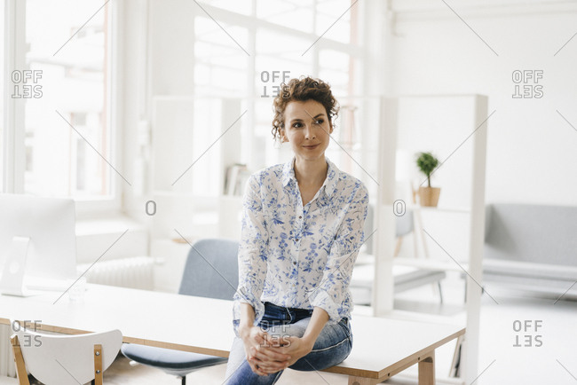 Businesswoman in office sitting on desk- looking confident