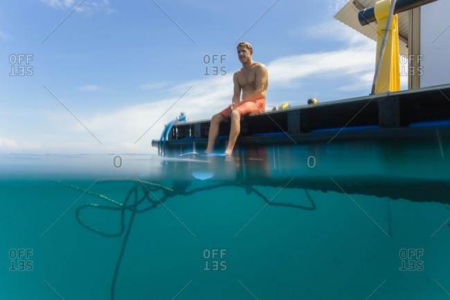 Man sitting on platform wearing flippers