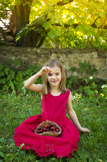 Portrait of little girl wearing red summer dress sitting on a meadow with basket of cherries