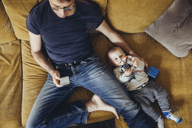 Baby boy lying on couch besides his father using smartphone