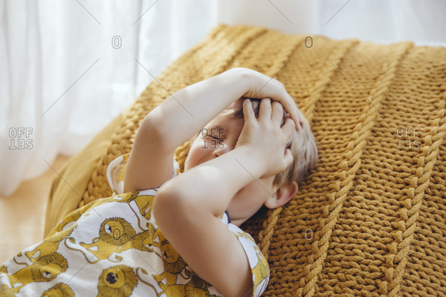 Little boy lying on cushion covering face with his hands