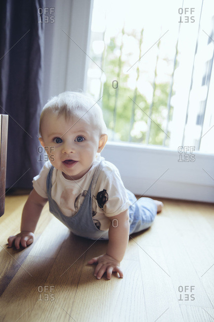 Portrait of baby boy crawling on the floor