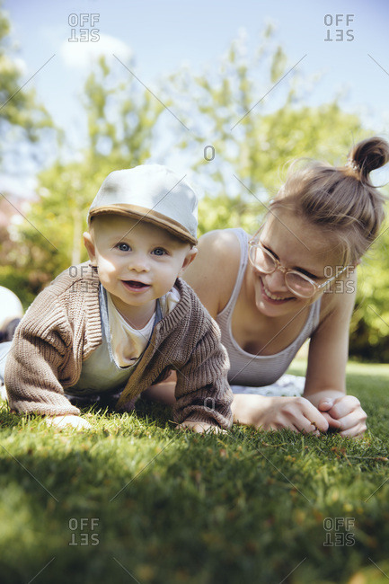 Portrait of baby boy with his mother on a meadow in the garden