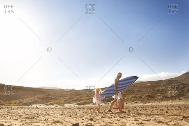Spain- Fuerteventura- mother and daughter walking with surfboard on the beach