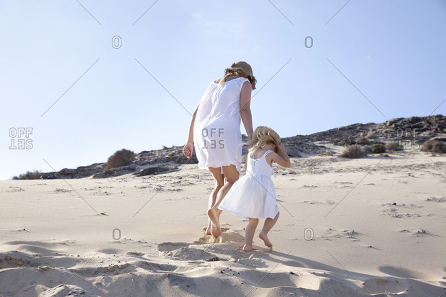 Spain- Fuerteventura- mother walking with daughter on the beach