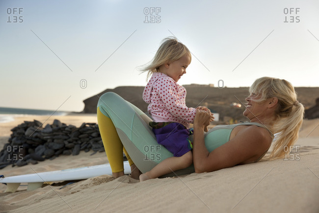 Spain- Fuerteventura- happy mother and daughter on the beach next to surfboard at sunset
