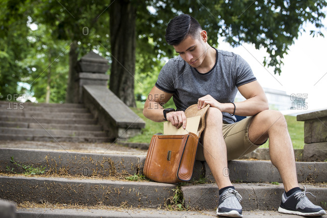 Young man sitting on stairs in park taking documents from bag