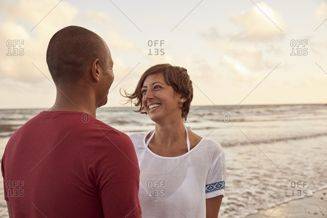 Couple in love face to face on the beach at evening twilight