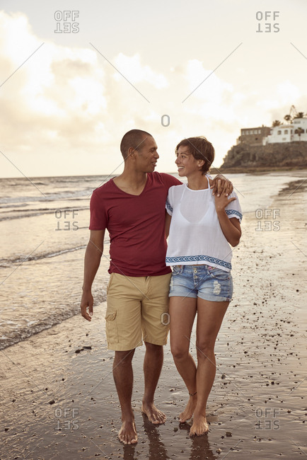 Couple in love strolling face to face on the beach at sunset