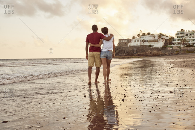 Spain- Canary Islands- Gran Canaria- back view of couple in love walking on the beach