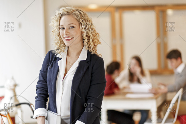 Portrait of confident businesswoman with a meeting in background